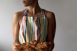 A woman in an apron holding pastries